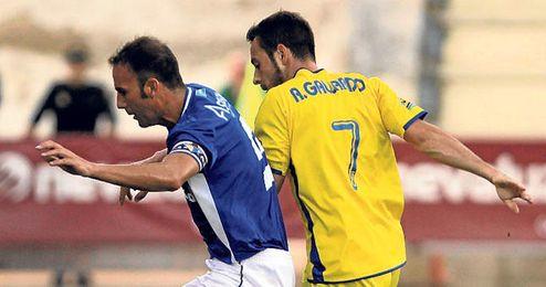Óscar Rodríguez, protege el balón ante un futbolista del Cádiz.