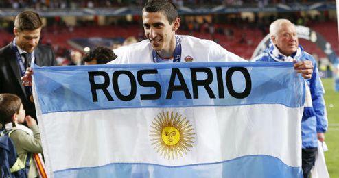 Di María celebra el título de Champions con la bandera de Argentina.
