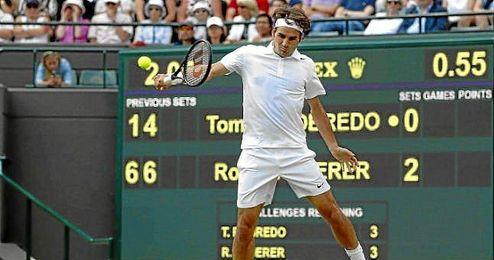 Federer golpea la bola durante un lance en el partido contra Robredo.