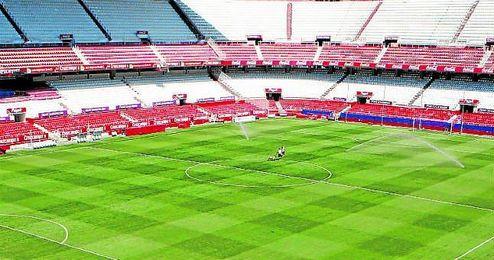 Operarios en el césped del estadio Ramón Sánchez Pizjuán.