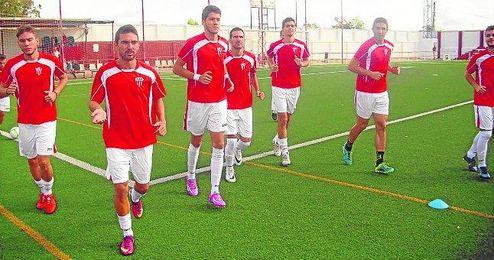 Enrique, el segundo por la derecha, realiza el calentamiento previo a un partido con sus compañeros en el estadio.