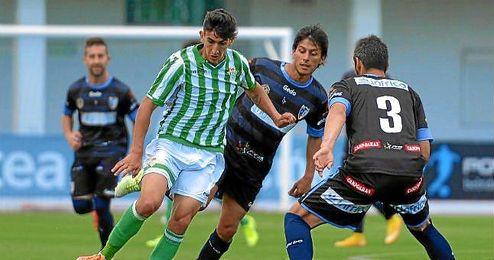 El verdiblanco Pibe lucha contra varios rivales durante el partido ante el Lucena.