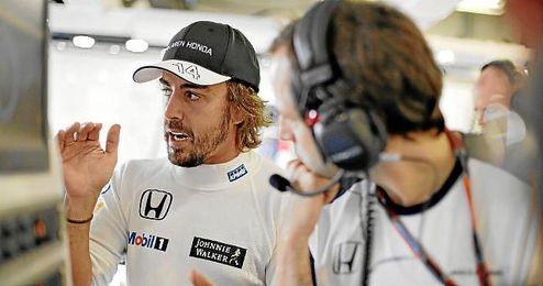 Alonso habla con uno de los ingenieros de su equipo.