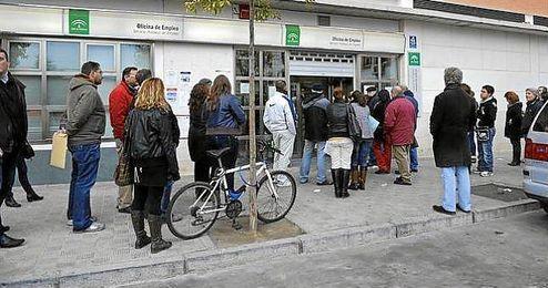 Personas guardando cola en la puerta de la Oficina de Empleo.
