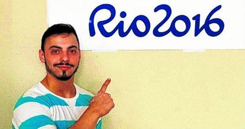 Josué Brachi señalando un cartel que hace referencia a las Olimpiadas de Río.