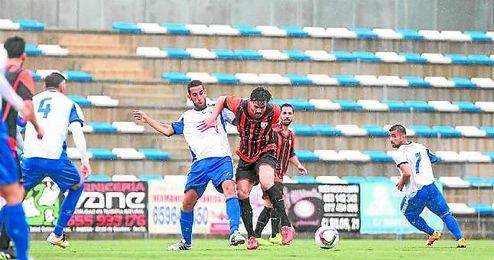 El ariete de la Lebrijana Chico protege el balón ante el centrocampista del Alcalá Manu Fidalgo.