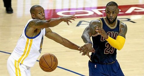LeBron James pasa un balón ante la presión rival.