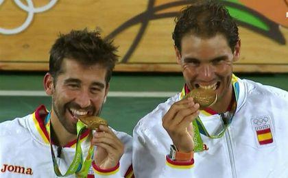 Rafa Nadal y Marc López muerden el oro conseguido.