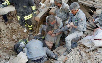 Los equipos de salvamento rescatan a una persona de entre los escombros.