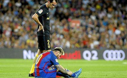 Messi, en el césped lesionado, bajo la mirada de Godín.