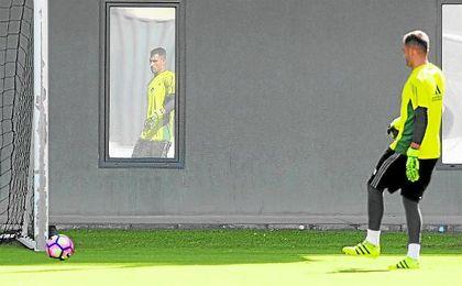 Ad�n, reflejado en una de las ventanas del edificio principal de la ciudad deportiva, ensaya un pase durante un entrenamiento.