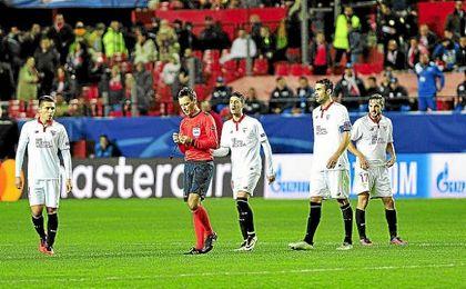 Varios jugadores del Sevilla protestan a Mark Clattenburg.