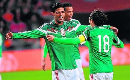 Carlos Vela se abraza con Guardado, con el que podría coincidir en el Betis, en un partido con México.