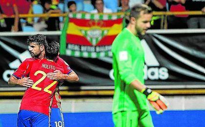 Costa celebra un gol con España con una bandera bética al fondo.