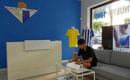 En la imagen, el surcoreano Kim firma su nuevo contrato con el Écija.
