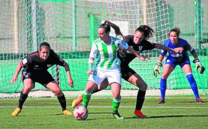 Paula Moreno, encimada por dos jugadores del Athletic durante el encuentro de este domingo.