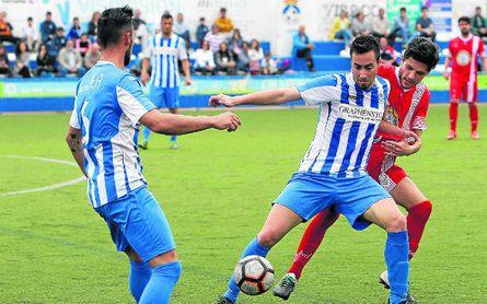 El blanquiazul Álex Pineda (derecha) controla el esférico ante la presión de un rival.