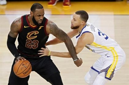 LeBron James lucha un balón con Stephen Curry.