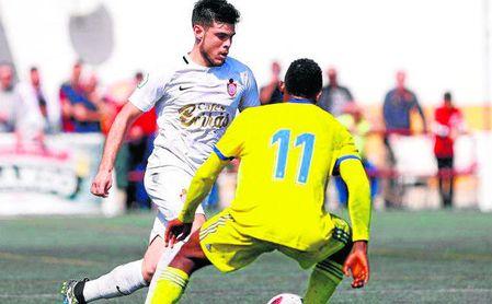 El futbolista utrerano Sergio Ortiz trata de marcharse del extremo cadista Peter.