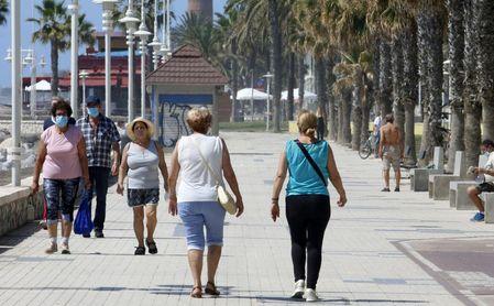 Paseantes disfrutan de la playa de Huelín durante la Fase 1 del Estado de Alarma.